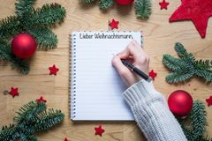 Writing Dear Santa in German on a notepad with Christmas decorat. Ions and fir branches on a wooden table from above Stock Image