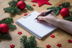 Writing Dear Santa on a notepad with Christmas decorations and f. Ir branches on a wooden table seen from the side Royalty Free Stock Images