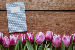 Writing diary in spring pink tulips and wood.  Royalty Free Stock Photos