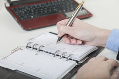 Writing down an appointment into diary. Someone writes a date of an appointment into his time schedule royalty free stock image