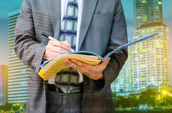 Writing down his ideas. Businessman with a document file Royalty Free Stock Photos