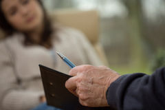 Writing down the history. Close-up of psychologist writing down patient's history royalty free stock photo