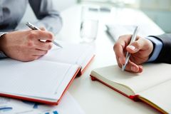 Writing down ideas. Close-up of male and female hands with pens over open notebooks at seminar Stock Photos