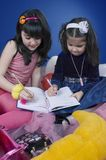 Writing down the ideas. Little girls writing in a big agenda, future business women Stock Images
