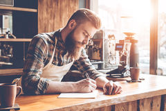 Writing down new coffee recipes. Stock Image