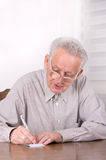 Writing down notes. Old man writhing down some notes on small paper Stock Images