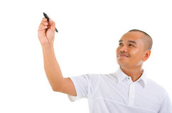 Writing or Drawing. Asian male in white shirt writing something on glass board with marker Royalty Free Stock Photo