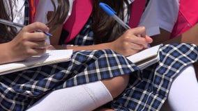 Writing dziewczyny Mniejszościowi ucznie Jest ubranym mundurki szkolnych Obraz Stock