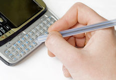 Writing e-mail on a mobile phone. Woman writing e-mail on a mobile phone keyboard Royalty Free Stock Photography