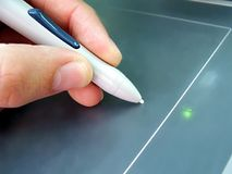 Writing on electronic tablet. Closeup of a hand holding a special pen, writing on an electronic tablet royalty free stock image