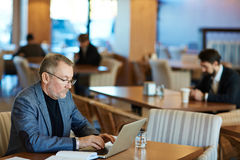 Writing Email to Business Partner. Bearded mature entrepreneur wearing eyeglasses writing email to his business partner on modern laptop while sitting in Stock Photo