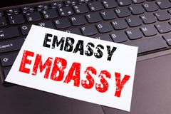 Writing Embassy text made in the office close-up on laptop computer keyboard. Business concept for Tourist Visa Application Worksh. Op on the black background Royalty Free Stock Images