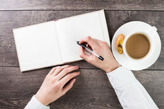 Writing on empty(blank) book(note, diary) spread mockup. A woman office worker hands writing on empty(blank) book(note, diary) spread mockup, top view, studio stock photos