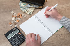 Writing a empty notepad with a calculator and some money Royalty Free Stock Images