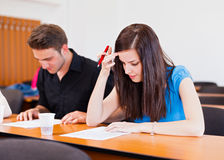 Writing Exam. Students at university writing test in classroom Stock Photos