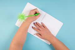 Writing with a fancy pen. Using a fancy green pen to write in a notebook Stock Images
