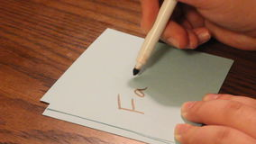Writing fat. Young women`s hand writing the word fat on a white card stock video footage