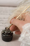 Writing with feather pen. Writer dip his feather pen into ink. Selective focus on ink and pen Stock Images
