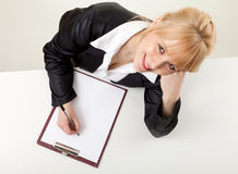Writing female student with clipboard Stock Image