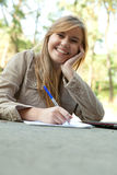 Writing female student outdoors Royalty Free Stock Photos