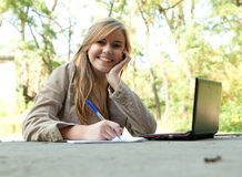 Writing female student working on laptop Royalty Free Stock Photos