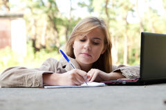 Writing female student working on laptop Stock Photography