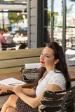 Writing and freelance concept. Female writer in outdoor cafe. Writing and freelance concept. Female writer wearing white shirt and polka dot skirt in outdoor stock images