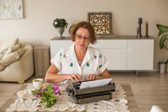 Writing and freelance. Middle age woman working from home. royalty free stock photography