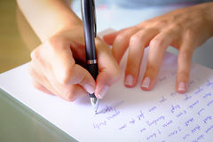 Writing. Girl Writing down a letter on a white sheet of paper with a black pen stock photos