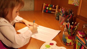 Writing girl. Little girl writing elementary homework stock video