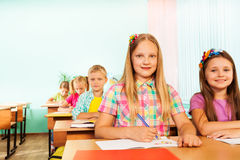 Writing girl looking straight and sitting at desk Stock Photo