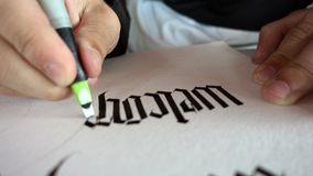 Writing Gothic calligraphy. Male hand writes with ink pen word `Welcome stock footage