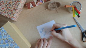 Writing a greeting card with a blue felt pen. Top view stock footage