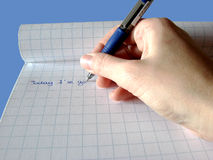 Writing hand. Hand writing with a pen on a note pad Royalty Free Stock Photo