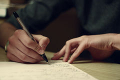 Writing hand. Men writes something on the paper, close-up Stock Photos