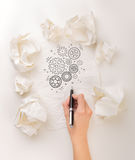 Writing hand in crumpled paper. Female hand next to a few crumpled paper balls drawing rotating gears Stock Photography
