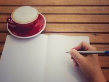 Hand writing on white paper with hot coffee in red cup on wooden table have space for texture. Writing hand on white paper with hot coffee in red cup on wooden Royalty Free Stock Image