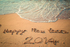 Writing Happy New Year's 2014 on the Beach Royalty Free Stock Images