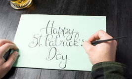 Writing a Happy St Patrick day calligraphy card. Male writing a Happy St Patrick day calligraphy card Royalty Free Stock Photo