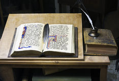 Writing of the historical book. Open old book on a table and a feather for the writing Royalty Free Stock Images