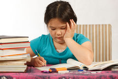 Writing Homework. Young girl having a hard time writing her homework Royalty Free Stock Photo