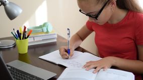 Writing homework in notebook. Beautiful young female student writing homework in notebook on the desk in her room stock video footage