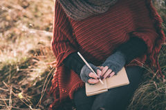 Writing ideas. Woman writing in the notebook Royalty Free Stock Image