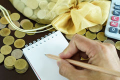 Writing income and expense on notebook Stock Images