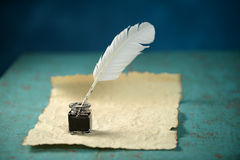 Writing Inkwell, Feather and Paper. Writing Inkwell with feather and vintage paper on table Royalty Free Stock Images