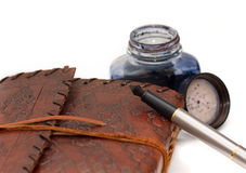 Writing in the journal. An antique/vintage journal with a fountain pen and pot of ink Stock Photography