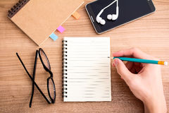 Writing a journal. Top view of right hand writing in blank notebook on wooded table with smartphone and glasses stock photography