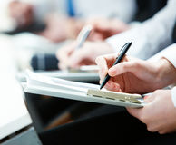 Writing lecture. Close-up of business person hands with documents writing at lecture Royalty Free Stock Photography