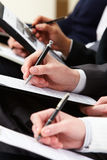Writing lecture. Close-up of business person hand with documents writing at lecture Royalty Free Stock Image