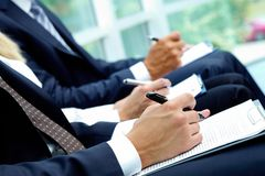 Writing lecture. Close-up of business people hands with papers writing at lecture royalty free stock photo